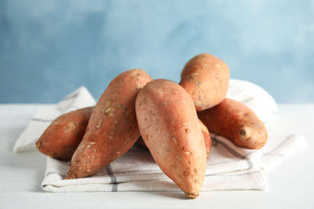 Sweet potatoes on table against color background