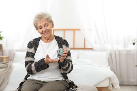 Senior woman using digital glucometer at home. Diabetes control
