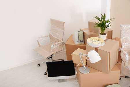 Moving boxes and furniture in new office. Space for text Stock Photo