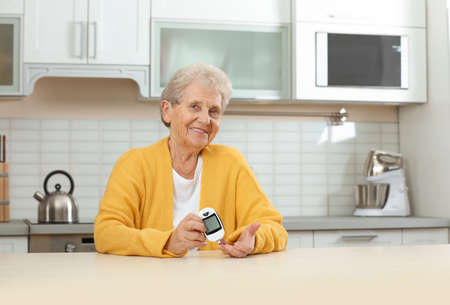 Senior woman using digital glucometer at home. Diabetes control Zdjęcie Seryjne