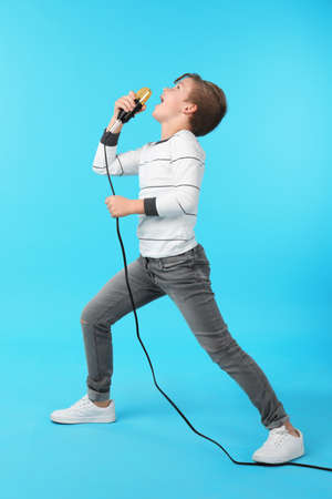 Cute boy singing in microphone on color background