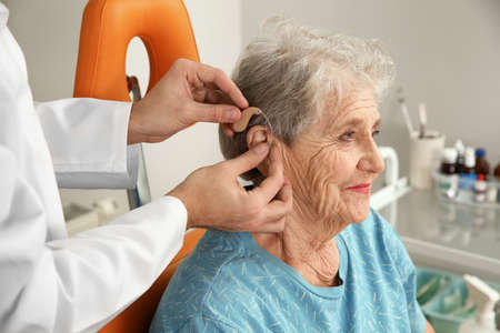 Otolaryngologist putting hearing aid in senior patients ear at clinic