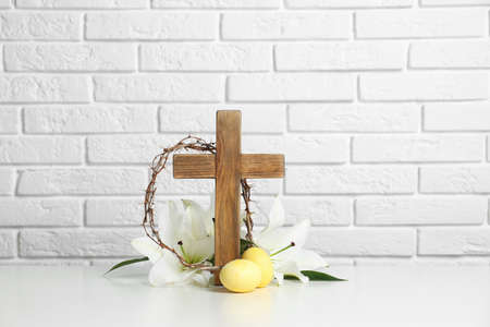 Wooden cross, crown of thorns, Easter eggs and blossom lilies on table against brick wall