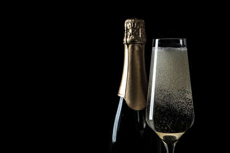 Bottle and glass of champagne on black background, space for text Standard-Bild