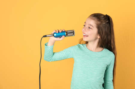 Cute girl singing in microphone on color background