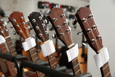 Row of different guitars in music store, closeup Imagens