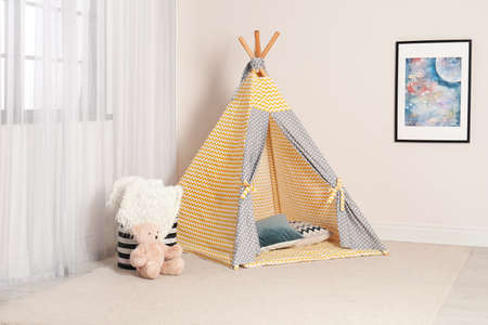 Cozy child room interior with play tent near window Фото со стока