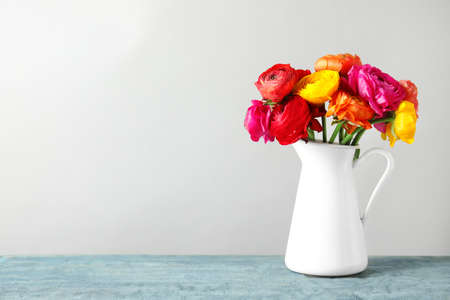 Vase with beautiful spring ranunculus flowers on table, space for text