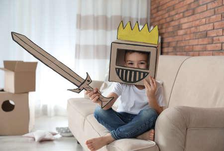 Cute little boy wearing cardboard armor in living room
