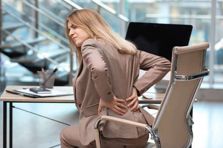 Young woman suffering from back pain in office Standard-Bild