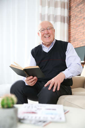 Elderly man reading book on sofa in living room Imagens