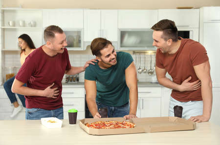 Group of friends with tasty food laughing together in kitchen