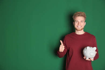Young man with piggy bank on color background, space for text. Money saving