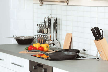 Clean frying pans and holder with knives in kitchen Foto de archivo
