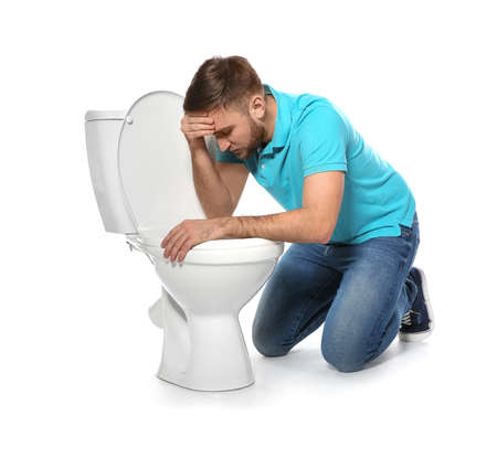 Young man suffering from nausea near toilet bowl isolated on white