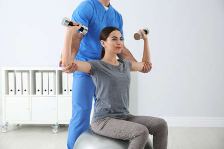 Doctor working with patient in hospital. Rehabilitation exercises Stockfoto