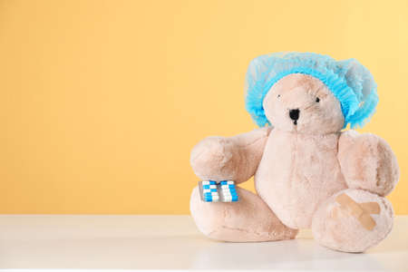 Toy bear with pills on table against color background, space for text. Children's hospital