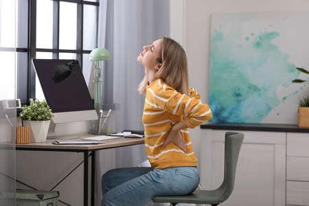 Jeune femme souffrant de maux de dos au bureau