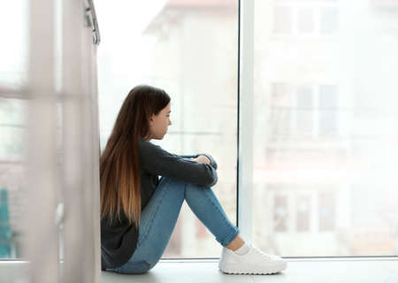 Upset teenage girl sitting at window indoors. Space for text Imagens