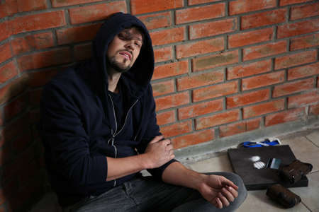 Joven adicto junto a la pared de ladrillo después de consumir drogas. Espacio para texto Foto de archivo