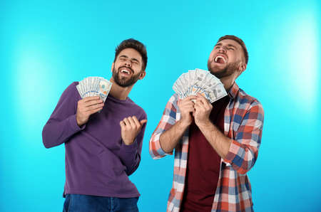 Happy young men with money on color background Stock Photo
