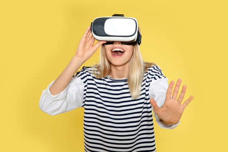 Emotional woman playing video games with virtual reality headset on color background