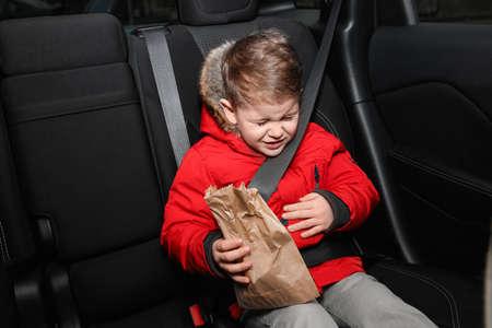 Kleine jongen met papieren zak die last heeft van misselijkheid in de auto