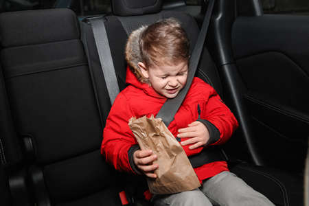 Little boy with paper bag suffering from nausea in car