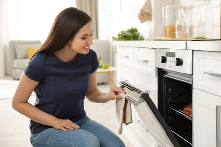 Beautiful woman opening door of oven with baked buns in kitchen