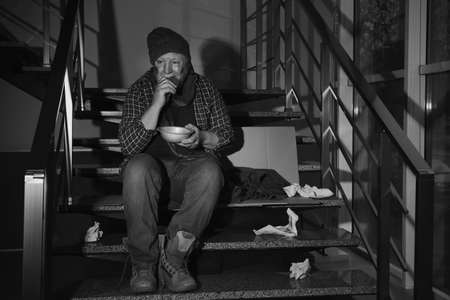 Poor senior man with bowl and bread on stairs indoors. Black and white effect