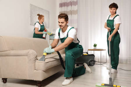Team of professional janitors working in living room. Cleaning service