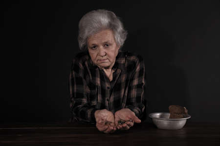 Poor mature woman with coins and bread in bowl at table