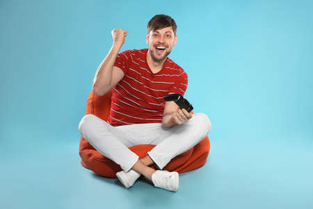 Emotional man playing video games with controller on color background Stock Photo