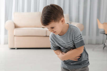 Little boy suffering from nausea in living room Stockfoto