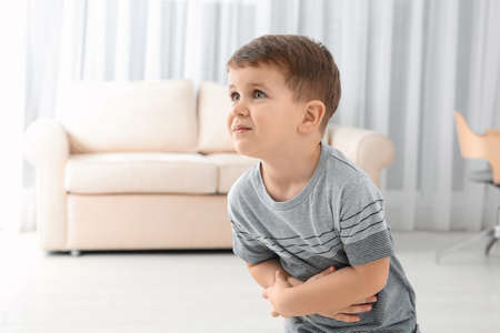 Little boy suffering from nausea in living room Imagens