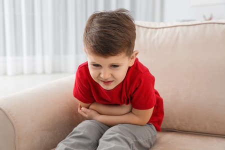Little boy suffering from nausea in living room