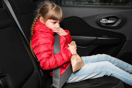Little girl with paper bag suffering from nausea in car