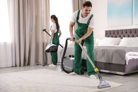 Team of janitors cleaning bedroom with professional equipment Imagens - 120493243