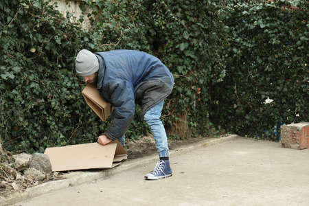 Poor homeless man with cardboard on street