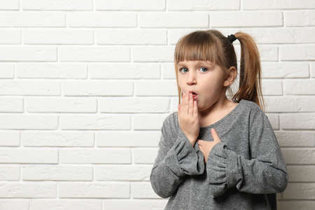 Cute little girl coughing near brick wall. Space for text