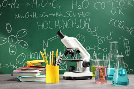 Laboratory glassware, microscope and stationery on table near chalkboard. Chemistry concept Stock Photo