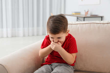 Little boy suffering from nausea in living room 版權商用圖片