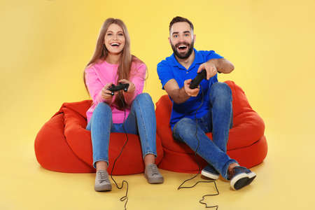 Emotional couple playing video games with controllers on color background