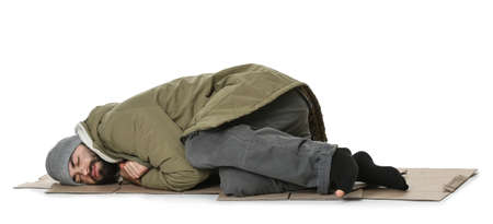 Poor homeless man lying on cardboard, white background