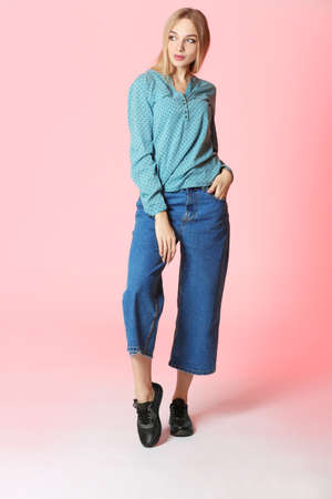 Fashionable young woman in stylish shoes on color background