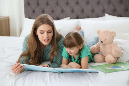 Young woman and her daughter reading book in bedroom. Helping to learn Banco de Imagens