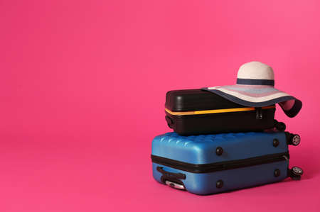 Stylish suitcases with hat on color background. Space for text