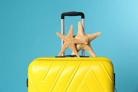 Stylish suitcase with sea stars on color background Stock Photo
