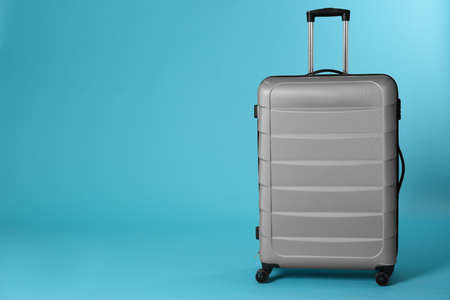 Stylish suitcase on color background. Space for text Stock Photo