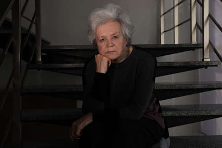 Portrait of poor mature woman sitting on stairs